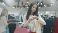 Happy young brunette girl is walking though a clothing store while checking notifications on her smartwatch. video