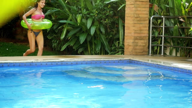 Happy young brunette sexy woman with an inflatable circle runs into the swimming pool in slow motion. 1920x1080 video