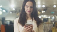 Happy young brunette woman is standing in a department store and using a smartphone. video