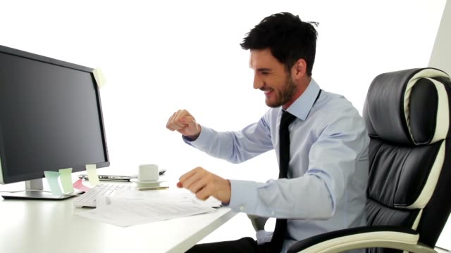 Happy young businessman dancing in his office video