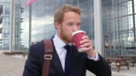 Happy young businessman walking with coffee in a city street video