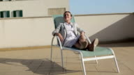 Happy young businesswoman relaxing on sunbed, tracking shot video