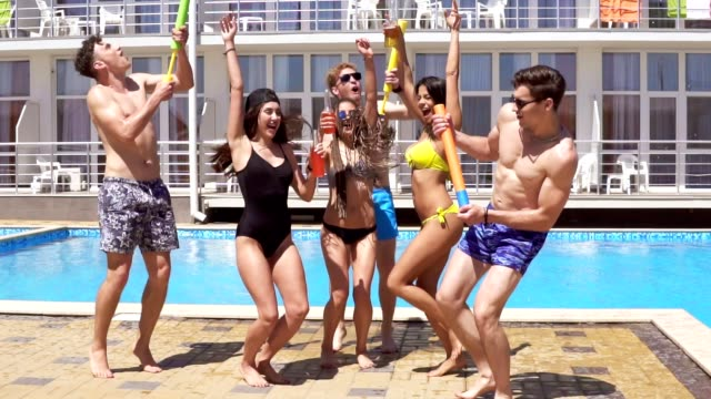 Happy young cheerful friends dancing and having fun at the pool. Summertime pool party. Slowmotion shot video