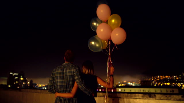 Happy young couple celebrates with colourful ballons on the rooftop video