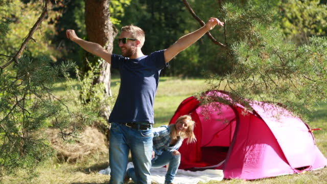 Happy young couple enjoying camping video
