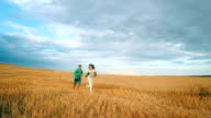 Happy young couple in love have romance and running through a wheat field in summer. Sunset, slow motion video