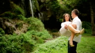 Happy Young Couple Playing in Front of Waterfall video
