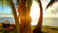 Happy young couple relaxing in tropical hammock at sunset video