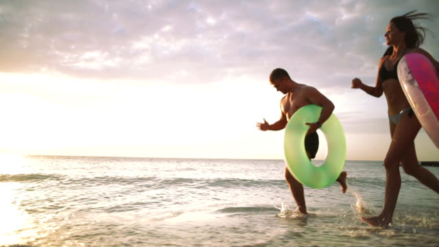Happy young couple runnung on the beach with rubber rings during sunset, slow motion video