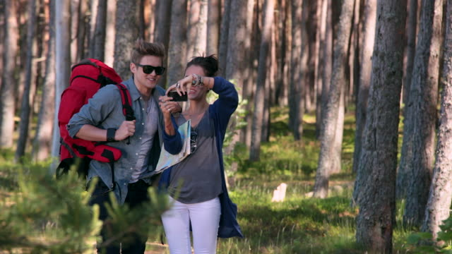 Happy young couple taking picture of themselves in nature video