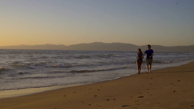 Happy young couple walking along sandy beach in ocean surf video