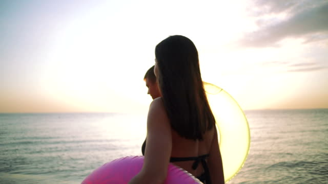 Happy young couple walking on the beach with rubber rings during sunset, slow motion video