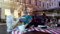 Happy young couple with tablet PC in a cafe video