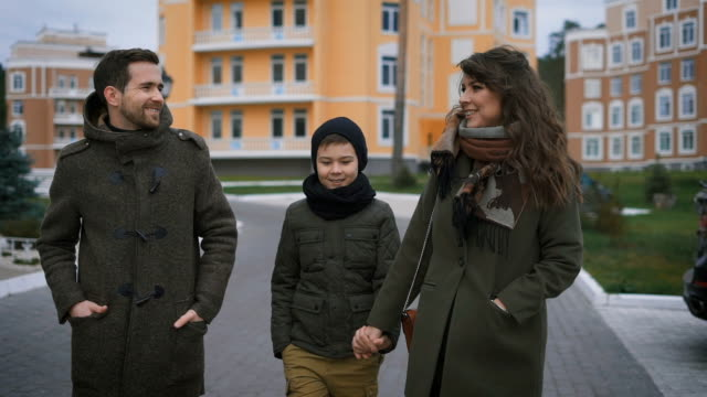 Happy young family in warm clothing are walking together on the street laughing and talking. Father, mother and son walking along the road looking happily to each other with buildings video