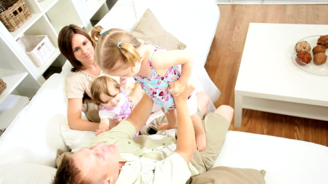 Happy Young Family Playing Together Home Couch video