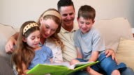Happy young family sitting on sofa looking at photo album video