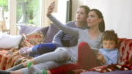 Happy young family taking selfies with her smartphone in home video