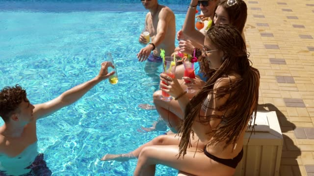 Happy young friends hanging out with coctails and chatting at the side of the pool in the summertime, drinking cocktails and doing cheers. Pool party. Shot in 4k video