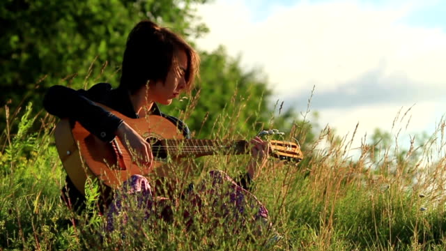 Happy young girl playing guitar outdoors. video