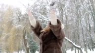 Happy young girl throwing up snow and laughing in the park. Slowly video