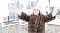 Happy young girl throwing up snow and laughing. Slowly video