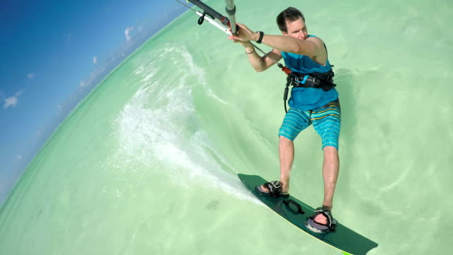CLOSE UP: Happy young kiter sportsman kiteboarding on perfect turquoise sea video