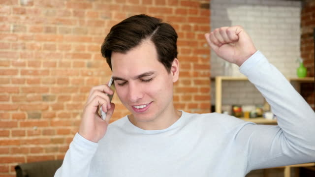 happy young man calling with mobile phone , joy excitment video