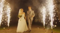 Happy young newlyweds are walking through fireworks in a park in the evening. video