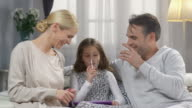 Happy young parents plays with daughter, using new technology in living room video