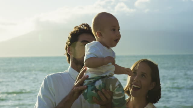 Happy young parents with baby boy in slow motion video