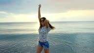 Happy young slim beautiful woman dancing on sunset beach. video