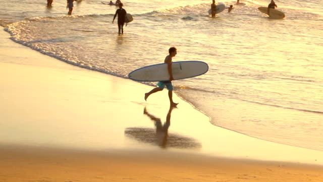 SLOW MOTION: Happy young surfer running with surfboard in hands into ocean video