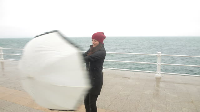 Happy young woman dancing with an umbrella in a rainy day. video