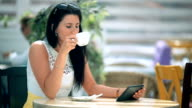 Happy young woman drinking coffee / tea and using tablet in a coffee shop video