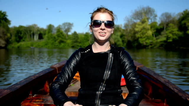 Happy young woman enjoying rowing boat on the lake video