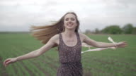 Happy young woman in dark dress with floral print having fun outdoor in geen field. Beauty girl spinning and laughing.wonderful smile.rotation middle shot ungraded flat color video
