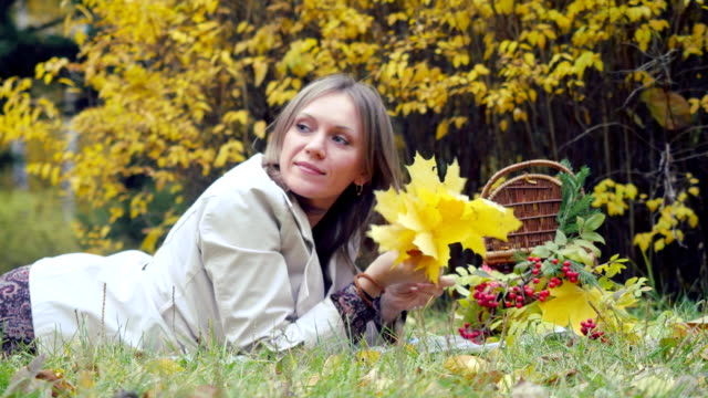 Happy young woman lying on autumn leaves near wicker basket in park holding bunch of leaves. 1920x1080 video