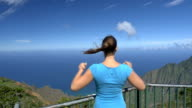 CLOSE UP: Happy young woman on lookout point outstretching arms victoriously video