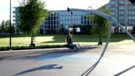 Happy young woman on tire swing in Helsinki park, slow motion video