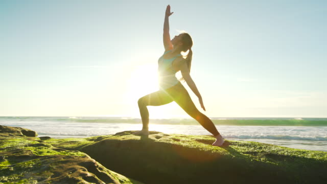 Happy young woman practicing yoga on the beach at sunset. Healthy active lifestyle concept. video