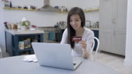 Happy young woman purchasing online through her laptop video