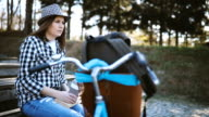 Happy young woman relaxing at park with bicycles video
