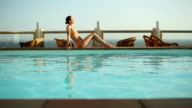 Happy young woman relaxing by the luxury swimming pool video