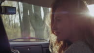 Happy young woman riding in car in forest video
