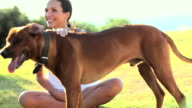 Happy young woman sitting with pet dog in a park video