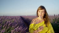 SLOW MOTION CLOSE UP: Happy young woman smelling scented lavender and smiling into camera video