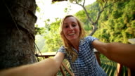 Happy young woman taking a selfie up in tree house video