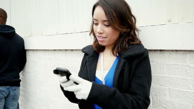 Happy young woman texting on smart phone outside in city video