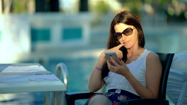 Happy young woman using a smart phone near the swimming pool video