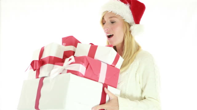Happy young woman wearing christmas hat and holding presents video